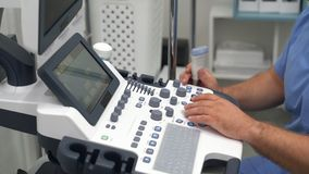 Ciérrese encima de las manos de los botones y de los trabajos de las prensas del doctor sobre el dispositivo del ultrasonido almacen de video