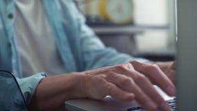 Ciérrese encima de las manos masculinas usando el ordenador portátil en la cocina Hombre joven que trabaja en el país metrajes