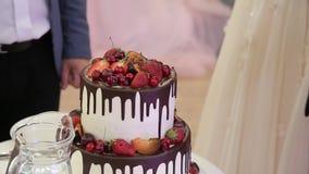 Ciérrese encima de las manos que cortan el pastel de bodas en el banquete de boda almacen de video