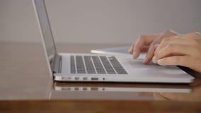 Ciérrese encima de las manos que enrollan director del banquero del panel táctil del ordenador portátil al principal almacen de video
