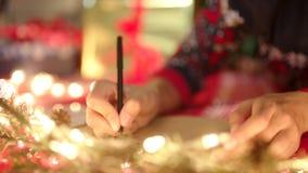 Ciérrese encima de las manos que escriben la letra de la Navidad a Santa Claus el Nochebuena metrajes