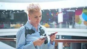 Ciérrese encima de las manos que sostienen la tarjeta de crédito y que usan el teléfono elegante móvil interior, compras en línea almacen de metraje de vídeo