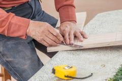 Ciérrese encima de las manos sucias del carpintero que trabajan con la regla y el lápiz Fotos de archivo