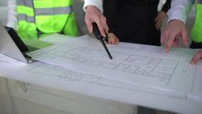 Ciérrese encima de las manos de tres trabajadores o ingenieros que discuten construyendo dibujos en oficina Tiroteo del primer de metrajes
