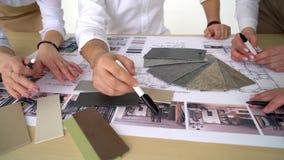 Ciérrese encima de las manos de tres trabajadores que discuten construyendo dibujos en oficina Tiroteo del primer de las imágenes metrajes