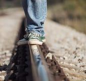 Ciérrese encima de las piernas de la imagen en sneackers en el ferrocarril Foto de archivo libre de regalías