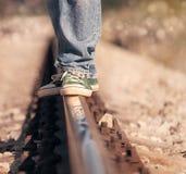 Ciérrese encima de las piernas de la imagen en sneackers en el ferrocarril Fotos de archivo