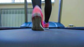 Ciérrese encima de las piernas de la mujer en zapatillas de deporte rosadas en a almacen de video