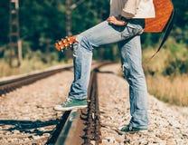 Ciérrese encima de las piernas del hombre de la imagen en zapatillas de deporte en ferrocarriles Fotografía de archivo libre de regalías
