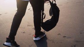Ciérrese encima de las piernas del hombre en paseos elegantes de las zapatillas de deporte en la arena brillante negra El individ metrajes