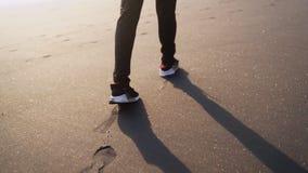 Ciérrese encima de las piernas del hombre en zapatillas de deporte elegantes que camina en la arena brillante negra y deja huella almacen de metraje de vídeo