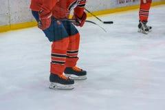 Ciérrese encima de las piernas del jugador de hockey en el hielo Foto de archivo