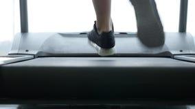 Ciérrese encima de las piernas del ` s de la mujer en una rueda de ardilla en el gimnasio metrajes