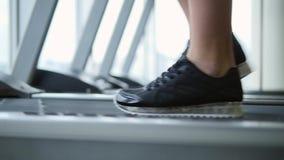 Ciérrese encima de las piernas del ` s de la mujer en una rueda de ardilla en el gimnasio almacen de metraje de vídeo