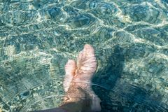 Ciérrese encima de las piernas descalzas del hombre de la imagen en la agua de mar imágenes de archivo libres de regalías