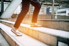 Ciérrese encima de las piernas de la gente que viaja que camina en el intensificación de la escalera i imagenes de archivo