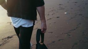 Ci?rrese encima de las piernas de los paseos del hombre en la arena brillante negra El individuo sostiene la mochila a disposici? metrajes