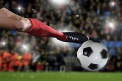 Ciérrese encima de las piernas y del zapato del fútbol del futbolista en la acción que golpea la bola con el pie que juega en est Imagenes de archivo