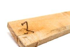 Ciérrese encima de los clavos doblados y oxidados de A que se pegaron en la placa de madera Fotografía de archivo libre de regalías