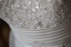 Ciérrese encima de los detalles de un vestido de la novia Fotografía de archivo libre de regalías