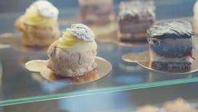 Ciérrese encima de los eclairs y de las tortas de chocolate en la vitrina de cristal metrajes