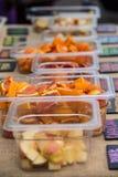 Ciérrese encima de los envases de manzanas y de naranjas cortadas Imágenes de archivo libres de regalías