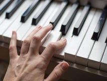 Ciérrese encima de los fingeres del pianista en las llaves del piano, el solo de los juegos de los brazos de la música o la nueva foto de archivo libre de regalías