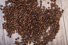 Ciérrese encima de los granos de café dispersados en el fondo de madera Imagen de archivo libre de regalías