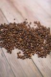 Ciérrese encima de los granos de café dispersados en el fondo de madera Foto de archivo libre de regalías