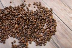 Ciérrese encima de los granos de café dispersados en el fondo de madera Imágenes de archivo libres de regalías