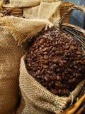 Ciérrese encima de los granos de café en una harpillera en una cesta fotografía de archivo