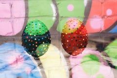Ciérrese encima de los huevos festivos de Pascua en la arpillera Huevos de Pascua coloridos en fondo rústico Huevos de la espuma  Imagenes de archivo