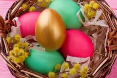 Ciérrese encima de los huevos de Pascua coloridos en cesta Imágenes de archivo libres de regalías