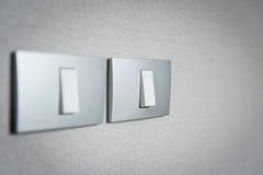 Ciérrese encima de los interruptores de la luz grises en fondo de la textura Imagen de archivo libre de regalías