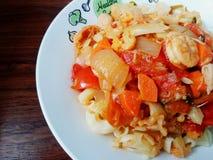 Ciérrese encima de los macarrones con el shirmp, los tomates, las cebollas y la zanahoria en el paladar blanco en la tabla de mad Foto de archivo libre de regalías