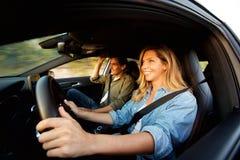 Ciérrese encima de los pares felices que sonríen en coche en viaje por carretera fotos de archivo