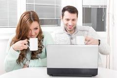 Ciérrese encima de los pares hermosos que trabajan en el ordenador portátil en casa foto de archivo