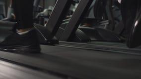 Ciérrese encima de los pies del hombre que caminan en el paso enérgico en la rueda de ardilla en el gimnasio, siguiendo izquierda almacen de video