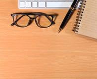 Ciérrese encima de los vidrios del ojo de la lectura en el hombre de negocios Wooden Table con Ot imagen de archivo libre de regalías