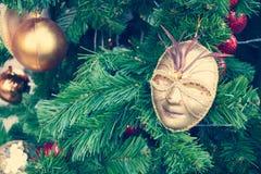 Ciérrese encima de máscara del oro en el árbol de navidad con el efecto retro del filtro (el estilo del vintage) Foto de archivo