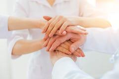 Ciérrese encima de mirada en los profesionales médicos que se unen a las manos juntas imagen de archivo libre de regalías
