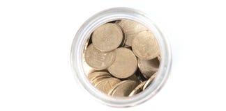 Ciérrese encima de monedas en el tarro de cristal en la tabla blanca Monedas dispersadas alrededor Aislado en el fondo blanco fotos de archivo