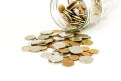 Ciérrese encima de monedas en el tarro de cristal en la tabla blanca Las monedas dispersaron arou imagen de archivo libre de regalías
