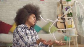 Ciérrese encima de mujer africana con un peinado afro se escapa del calor delante de una fan corriente MES lento metrajes