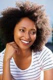 Ciérrese encima de mujer africana joven con el pelo rizado que parece ausente y que sonríe al aire libre imagenes de archivo