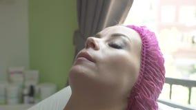 Ciérrese encima de mujer hermosa en salón de belleza Mujer joven en clínica cosmética Cosmetología y tratamiento profesionales ad almacen de video