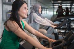Ciérrese encima de mujeres de la visión en el gimnasio que hace ejercicios cardiios Foto de archivo
