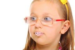 Ciérrese encima de niña en los vidrios que hacen burbujas de la saliva de la diversión foto de archivo