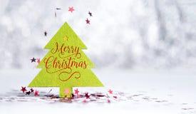 Ciérrese encima de palabra de la Feliz Navidad en el árbol de navidad verde con la chispa Fotos de archivo