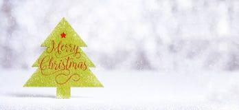 Ciérrese encima de palabra de la Feliz Navidad en el árbol de navidad verde con la chispa Foto de archivo